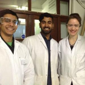 Four medics right after a dissection session, smiling for the camera